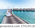 Asian woman holding pegasus pool float at Maldives. 37414518