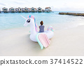 Asian woman sit on pegasus pool float at Maldives. 37414522