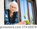 Pensive grandma at the home window 37416978