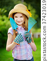 Adorable little girl wearing straw hat and childrens garden gloves holding garden tools 37423019