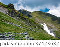 rocky cliffs on grassy slopes with snow in summer 37425632