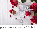 Fresh red roses and gift box on wooden table 37426645