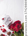 Fresh red roses and gift box on wooden table 37426669