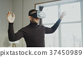 Excited man with virtual reality headset playing 37450989
