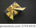 Gift box with gold ribbon on black surface. 37454930