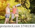 Blond boy looking in a large pair of binoculars 37481916