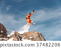 An athlete skier is jumping from high rock high in 37482206