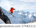 A professional skier makes a jump-drop from a high 37482212