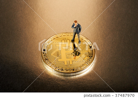 Miniature businessman standing on a Bitcoin 37487970