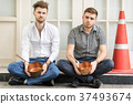 Two men sitting on the sidewalk  holding a pot. 37493674