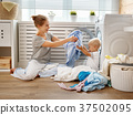 Happy family mother   housewife and   baby son in   laundry load 37502095