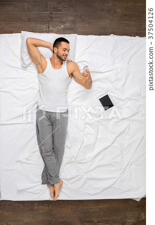 Young man relaxation on the bed top view 37504126