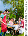Man grilling meat on garden barbecue party 37511157
