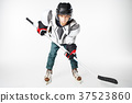 Young hockey player in safety gear with stick 37523860