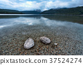 Two rocks in the shallow lake. 37524274
