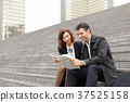 engineers male and female reading article a 37525158