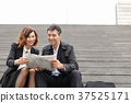 engineers male and female reading article a 37525171