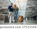 Smiling man and woman paying for boarding pass 37525566