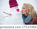 Cheerful young woman having fun with snowman 37525966