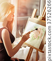 Artist painting on easel in studio. Girl paints 37526266