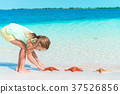 Adorable little girl with wild red starfish on 37526856