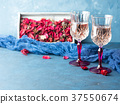 Two stemmed glasses with champagne on blue 37550674