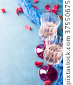 Two stemmed glasses with champagne on blue 37550675