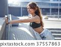 Long haired sporty girl exercises on city street 37557863
