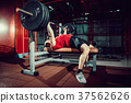 Man doing bench press workout in gym 37562626