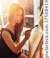Artist painting on easel in studio. Girl paints 37568419