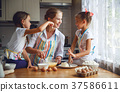 Happy family mother and children twins   bake kneading dough in 37586611