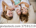 three girls in the morning lying in bed 37591219