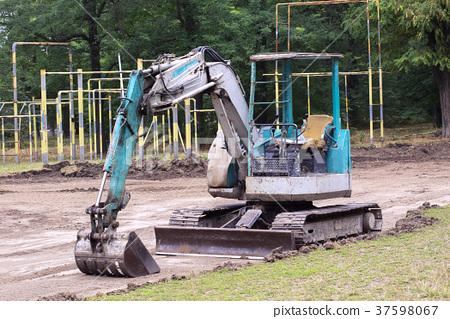 Small excavator at work making garden pond 37598067