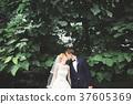 Stylish couple of happy newlyweds walking in the 37605369