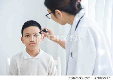 Doctor wear glasses checking a little boy patient eyes. 37605947