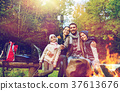 family with smartphone taking selfie near campfire 37613676