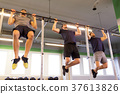 group of young men doing pull-ups in gym 37613826