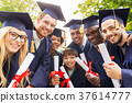happy students in mortar boards with diplomas 37614777