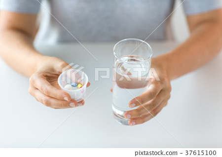close up of hands with pills and glass of water 37615100