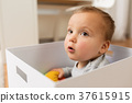 close up of sweet little baby boy in toy box 37615915