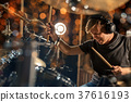 male musician playing drum kit at concert 37616193