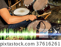 male musician playing drum kit at concert 37616261