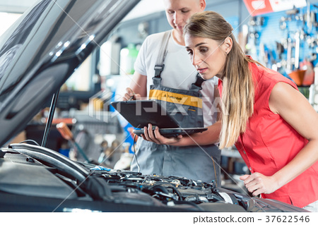 Auto mechanic showing to a customer the engine 37622546