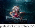 Woman plays music diving under the water. 37627755