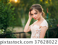 Young girl in wedding dress in park posing for 37628022