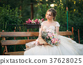 Young girl in wedding dress in park posing for 37628025