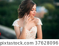 Young girl in wedding dress on city background at 37628096