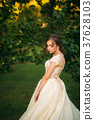 Young girl in wedding dress in park posing for 37628103