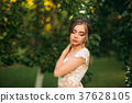 Young girl in wedding dress in park posing for 37628105