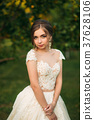 Young girl in wedding dress in park posing for 37628106